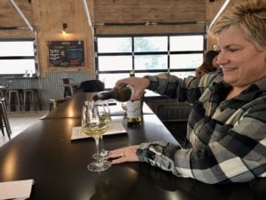 Lady pouring wine into glasses