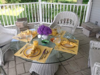 Porch table with a setting and flower centerpiece