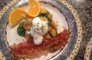 Poached Egg on top of Herbed Potatoes, Bacon and an Orange