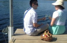 Couple having a picnic on the dock by the lake