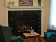 two blue chairs in front of fireplace