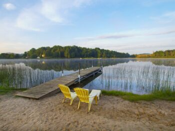 two yellow chairs on sand next to pier jutting out into calm lake